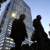 Pedestrians walk past the headquarters of Toshiba Corp. in central Tokyo in December 2010. | BLOOMBERG
