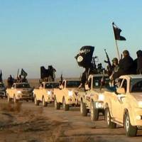 In this undated file photo released by a militant website, which has been verified and is consistent with other AP reporting, militants of the Islamic State group hold up their weapons and wave flags as they ride in a convoy, which includes multiple Toyota pickup trucks, through Raqqa city in Syria on a road leading to Iraq. Toyota is working with U.S. officials after questions were raised about the prominent use of its vehicles by militant organizations in Syria, Iraq and Libya. | MILITANT WEBSITE VIA AP