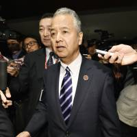 Economy minister Akira Amari is mobbed by reporters after a Trans- Pacific Partnership ministerial meeting on Friday. | KYODO