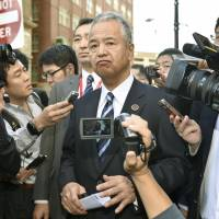 Trade minister Akira Amari fields questions from reporters in Atlanta on Thursday, following the first day of talks on the Trans-Pacific Partnership. | KYODO