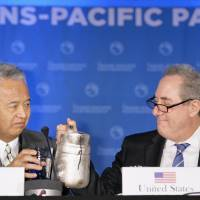 U.S. trade representative Michael Froman pours a glass of water for economy minister Akira Amari during the Trans-Pacific Partnership talks in Atlanta on Monday. | KYODO