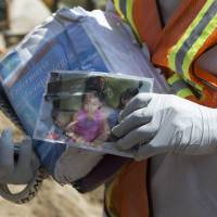 Samuel Morales, who survived a mudslide but is still searching for his missing family, holds a photo of his 4-year-old daughter, Jaquelin, in Cambray, a neighborhood in the suburb of Santa Catarina Pinula on the outskirts of Guatemala City, on Friday. | AP