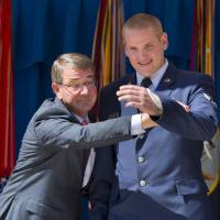 Defense Secretary Ash Carter raises the injured left arm of Airman 1st Class Spencer Stone on Sept. 17 before Stone received the Airman's Medal and Purple Heart medal, during a ceremony at the Pentagon in Washington. An Air Force spokesman says Stone, who helped subdue an attacker on a Paris-bound train in August, is in stable condition after being stabbed in California. | AP