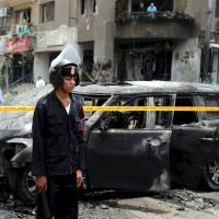 Police investigate a car-bomb attack on the convoy of public prosecutor Hisham Barakat near his house in the Heliopolis district of Cairo on June 29. Former special forces officer Hisham al-Ashmawy is blamed for the bombing and other high-profile attacks in Egypt. | REUTERS