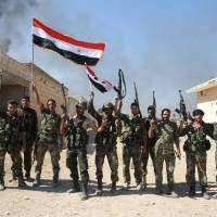 Syrian army units and pro-government forces deploy at an undisclosed location in the Atshan village in central province of Hama on Sunday. | AFP-JIJI