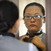 Chinese butler school graduate Zhang Zhejing ties her necktie in a hotel room as she prepares for a day of butler duties at a conference in Beijing on Sept. 25. | AP