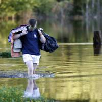 Sean Nance walks through floodwaters carrying some work clothes as he evacuates from his apartment in the Ashborough subdivision near Summerville, South Carolina, Tuesday. Residents are concerned that the Ashley River will continue to rise as floodwaters come down from Columbia. | AP
