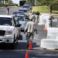 National Guard members hand out water to residents in Columbia, South Carolina, Tuesday. Water distribution remained a key problem Tuesday across much of the state. In Columbia, as many as 40,000 homes lacked drinking water, and the rest of the city's 375,000 customers were told to boil water before using it for drinking or cooking. | AP