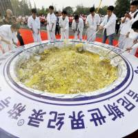 Participants stir a giant bowl of fried rice during a Guinness World Record attempt on Thursday in Yangzhou, Jiangsu province, China. A total of 4,192 kilograms of fried rice was cooked, but some of it was spoiled and was fed to pigs. | REUTERS