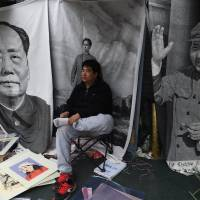A vendor waits for customers to buy wall hangings depicting late Communist Party Chairman Mao Zedong at a market in Beijing on Sunday. A Chinese military newspaper says that unnamed forces in the West are trying to falsify the party's and the military's history. | AFP-JIJI