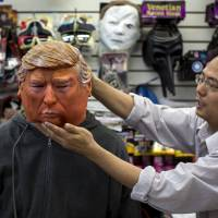 Store Manager Sunny Wong adjusts a Halloween mask of Republican presidential candidate Donald Trump on employee Kenny Lomi as he poses for a photo at the Village Party Store halloween headquarters in the Manhattan borough of New York Thursday. Trump and GOP rival Ben Carson are threatening to boycott next week's party debate over broadcast issues. | REUTERS
