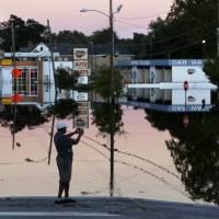 Gay Miller takes photos of E. Main Street in downtown Kingstree, South Carolina, Wednesday as the Black River floodwaters reflect in the later afternoon light. | AP
