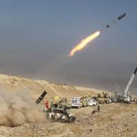 Iraqi Shiite fighters from the Popular Mobilization units, fighting alongside Iraqi forces, fire a rocket during a military operation against Islamic State  group jihadists as they advance toward the center of Baiji Sunday. | AFP-JIJI