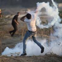 A Palestinian protester throws a tear gas canisters back during clashes with Israeli soldiers by the Israeli border with Gaza in Buriej, central Gaza Strip, Thursday. | AP
