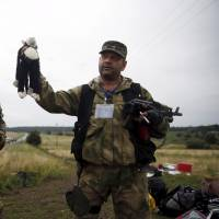 A pro-Russian separatist holds a stuffed toy found at the crash site of Malaysia Airlines Flight MH17 on July 18, 2014. | REUTERS