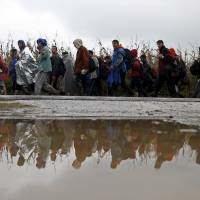 Cold, mud-caked thousands swarm Croatia after border with Serbia suddenly opens