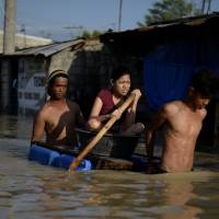 Residents use a raft made of jerry cans to cross a flooded street in Calumpit, Bulacan province, in the Philippines on Thursday. The death toll from Typhoon Koppu climbed to 54 on Thursday, as floods shifted downstream to coastal villages, displacing tens of thousands of residents. | AFP-JIJI