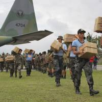 Philippine troops unload a military plane carrying relief aid at an airport in Baler province, in the northern Philippines on Wednesday. Typhoon Koppu left several people dead and forced more than 100,000 villagers into emergency shelters. It also destroyed rice crops ready for harvest. | AP