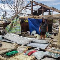 A resident stands in front of a house destroyed by Typhoon Koppu in Casiguran town, northeast of Manila, on Wednesday.  | AFP-JIJI