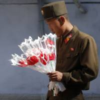 A soldier looks at decorative flowers outside of a shop Friday, ahead of Saturday's anniversary celebrations in Pyongyang. The country was preparing for the 70th anniversary of the founding of the North Korea Workers' Party on Saturday. | AP
