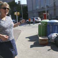 Caroline Bragdon, a rat expert with New York City's Department of Health and Mental Hygiene, points out garbage containers near a park Sept. 17 in the Chinatown neighborhood of New York. The city's complaint hot-line is on pace for a record year of rat calls, exceeding the more than 24,000 over each of the last two years. | AP