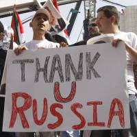 Supporters of the Syrian government hold a pro-Russian banner Monday as they show their support for Syrian President Bashar Assad and to thank Russia and China for blocking a U.N. Security Council resolution condemning Syria for its brutal crackdown, during a demonstration in Damascus. | AP