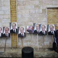 Photos of Syrian President Bashar Assad and Russian President Vladimir Putin are propped against a wall during a pro-Syrian government protest in March 2013 in front of the Russian Embassy in Damascus. | AP