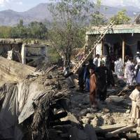Pakistani residents gather next to the rubble of earthquake-damaged houses in Lower Dir on Tuesday. Rescuers were picking their way through rugged terrain and pockets of Taliban insurgency in the search for survivors after a massive quake hit Pakistan and Afghanistan, killing more than 350 people. | AFP-JIJI