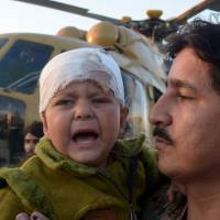 A Pakistani army officer carries a young injured earthquake survivor who was evacuated from Chitral by military helicopter at a base in Peshawar on Tuesday. | AFP-JIJI