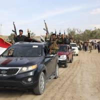 Sunni volunteer fighters parade as they prepare to support Iraqi security forces in liberating the city of Ramadi from Islamic State group militants, in Khalidiya, 60 miles (100 km) west of Baghdad, Saturday. | AP