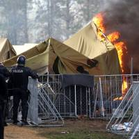 Cold, rain-soaked refugees crowding Slovenia camp demand transit, wage fiery protest