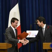 French Prime Minister Manuel Valls and Prime Minister Shinzo Abe shake hands at the end of a joint news conference in Tokyo on Monday evening. | AP