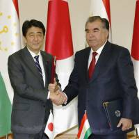 Prime Minister Shinzo Abe shakes hands with Tajikistan President Emomali Rahmon following their meeting in Dushanbe on Saturday. | KYODO