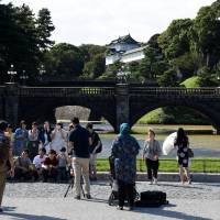 Tourists pose for photos in front of what is commonly known as Nijubashi Bridge, on Sept. 30 in Tokyo's Chiyoda Ward. | SATOKO KAWASAKI
