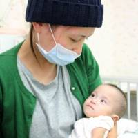 A highly premature baby born with tetralogy of Fallot is embraced by her mother at Okayama University Hospital on Friday after surgery to treat the congenital heart defect. | KYODO