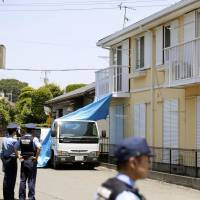 Police officers in June 2014 inspect the apartment building where Riku Saito's skeletal remains were found some seven years after the 5-year-old died of malnutrition in a room where he was locked up by his father. | KYODO