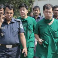A Japanese doctor (front right) and the chief security officer of the Japanese Embassy in Bangladesh (center) walk back from the morgue after an autopsy on Japanese citizen Kunio Hoshi in Mahiganj, Bangladesh, on Sunday. | AP