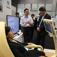 Visitors to an August trade show in Koto Ward, Tokyo, try out a computer-controlled Smartchair prototype jointly developed by Nagoya University and Panasonic Corp. | CHUNICHI SHIMBUN
