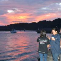 Protestors gather in Taiji, Wakayama Prefecture, in September as boats leave for the season's first dolphin hunt. | KYODO