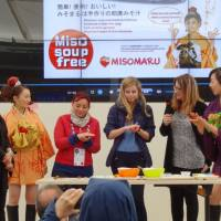 Yokohama resident Tomoko Fujimoto (second from left) shows visitors to the Japan Pavilion how to make a misomaru (a roll of fermented soybean paste with filling), at Expo Milano 2015 in May. Visitors were able to sample miso soup made from the roll. | KYODO