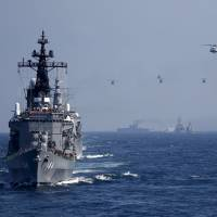 The Maritime Self-Defense Force destroyer Kurama (left) carrying Prime Minister Shinzo Abe leads other vessels and helicopters during a fleet review in Sagami Bay off Yokosuka, Kanagawa Prefecture, on Sunday. | REUTERS