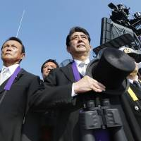 Prime Minister Shinzo Abe, accompanied by Defense Minister Gen Nakatani (left) and Deputy Prime Minister Taro Aso (second left), holds his hat during a Maritime Self-Defense Force fleet review aboard the destroyer Kurama in Sagami Bay off Kanagawa Prefecture on Sunday afternoon. | KYODO