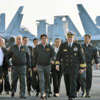 Prime Minister Shinzo Abe, along with Defense Minister Gen Nakatani (second from left) and Deputy Prime Minister Taro Aso (second from right), tours the USS Ronald Reagan, led by commanding officer Christopher Bolt (fourth from right) in Sagami Bay, off Kanagawa Prefecture, on Sunday afternoon. | POOL/KYODO