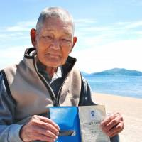 Ichio Isobe holds a radiation control notebook issued when he worked in the 1970s at the Fukushima No. 1 nuclear power plant, in May on Iwai Island, Yamaguchi Prefecture. In the background is Tanoura, the construction site for the planned Kaminoseki nuclear power plant. | KYODO