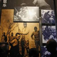 Visitors look at photos on display at the Nanjing Massacre Memorial Hall in Nanjing on Oct. 10. Japan has lashed out at UNESCO's decision to inscribe China's 'Documents of Nanjing Massacre' in its Memory of the World program, describing it as 'extremely regrettable' and calling for the process to be reformed. | AFP-JIJI