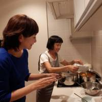 Sachiko Wada, who heads the Taskaji online matching service, chats with her Filipino housekeeper as she cooks dinner at her home in Tokyo last month. | ATSUSHI KODERA