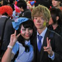 A couple wearing Halloween make-up pose for a photo in Hachiko Square in front of JR Shibuya Station in Tokyo on Saturday night. | YOSHIAKI MIURA