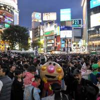 A large crowd of Halloween revelers mill about in Hachiko Square in front of JR Shibuya Station in Tokyo on Saturday night. | YOSHIAKI MIURA