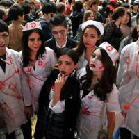 A group of Halloween revelers dressed as zombie hospital staff pose for a photo Saturday evening in Hachiko Square in front of JR Shibuya Station in Tokyo. | YOSHIAKI MIURA