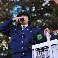 Speaking through a public address system, a policewoman verbally gives guidance commands to the large crowd of Halloween revelers at Hachiko Square in front of JR Shibuya Station in Tokyo. | YOSHIAKI MIURA